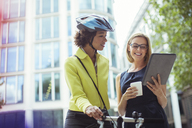 Businesswomen using digital tablet outdoors - CAIF14596