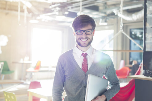Portrait of confident businessman holding laptop in sunny office - CAIF14611