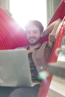 Casual businessman using laptop in hammock in sunny office - CAIF14614
