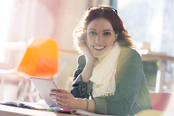 Portrait of smiling casual businesswoman using digital tablet - CAIF14653