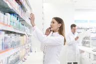Pharmacist talking on cell phone and removing box from shelf in pharmacy - CAIF14686