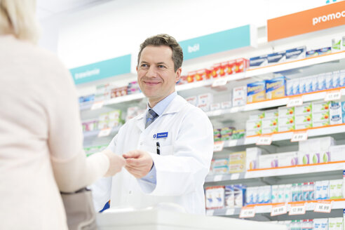 Smiling pharmacist assisting customer in pharmacy - CAIF14692