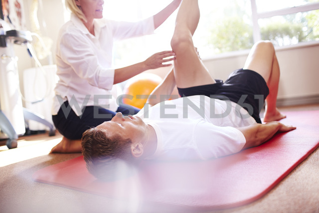 Physical therapist stretching man's leg - CAIF14749