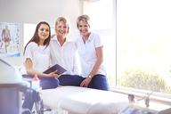 Portrait smiling physical therapists in examination room - CAIF14752