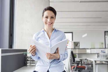 Portrait smiling businesswoman holding report in office - CAIF14758