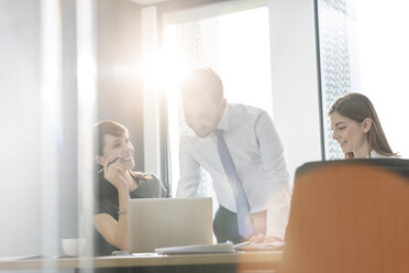 Business people working at laptop in sunny conference room meeting - CAIF14761