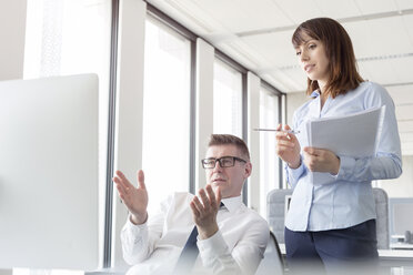 Businessman at computer gesturing and explaining to businesswoman in office - CAIF14767