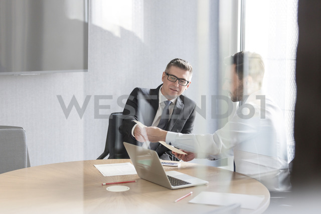 Businessmen discussing paperwork at laptop in conference room - CAIF14773 - Agnieszka Wozniak/Westend61