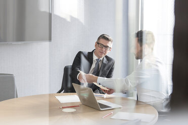 Businessmen discussing paperwork at laptop in conference room - CAIF14773