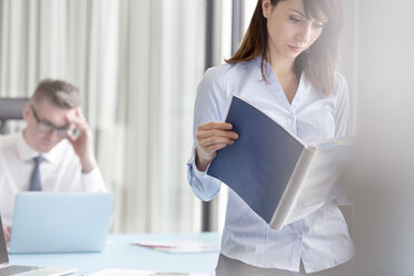 Focused businesswoman reading report in office - CAIF14776