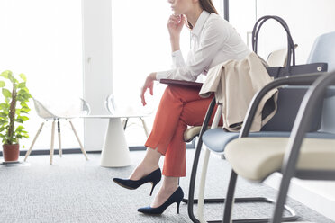 Businesswoman waiting with legs crossed in lobby - CAIF14779