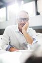 Smiling older man sitting at desk - CAIF14797