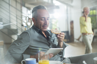 Older man using digital tablet at breakfast table - CAIF14806