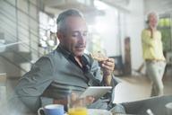 Older man using digital tablet at breakfast table - CAIF14806