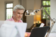 Older man using laptop in home office - CAIF14815