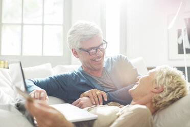 Older couple relaxing together on sofa - CAIF14824