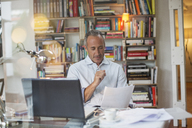 Businessman reading paperwork at home office desk - CAIF14830