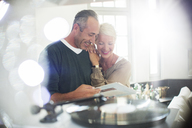Older couple listening to vinyl records - CAIF14845
