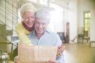 Older woman hugging husband reading newspaper - CAIF14851