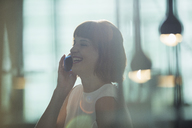 Businesswoman talking on cell phone in office - CAIF14863