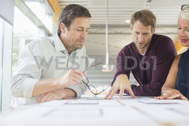 Business people reading paperwork in office meeting - CAIF14890