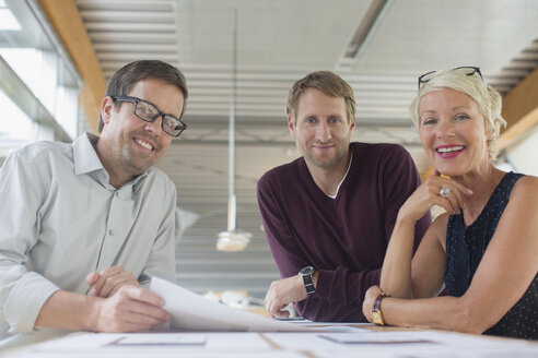 Business people smiling in office meeting - CAIF14902