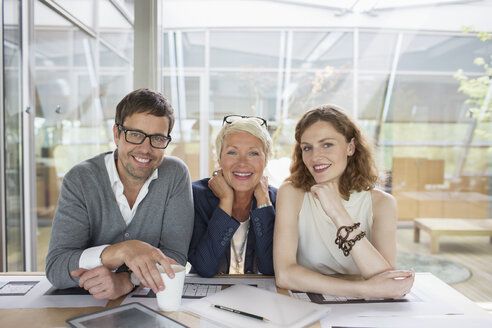 Business people smiling in office meeting - CAIF14908