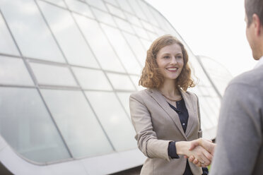 Business people shaking hands outdoors - CAIF14917