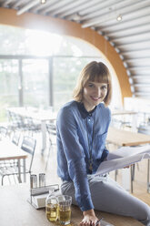Businesswoman smiling in cafeteria - CAIF14965
