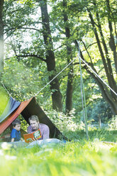Father and son reading in camping tent - CAIF14986