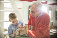 Grandfather and grandson building model sailboat - CAIF15004