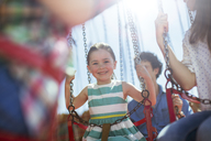 Girl smiling on carousel in amusement park - CAIF15016