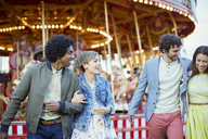 Two couples walking in amusement park and laughing - CAIF15019
