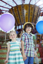 Portrait of boy and girl holding balloons in amusement park - CAIF15025