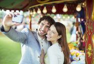 Smiling couple taking selfie in amusement park - CAIF15037