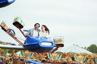 Couple enjoying ride on carousel in amusement park - CAIF15043
