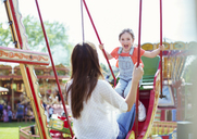 Mother and daughter playing on swing in amusement park - CAIF15046