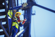 Low angle view of workers talking on crane - CAIF15082