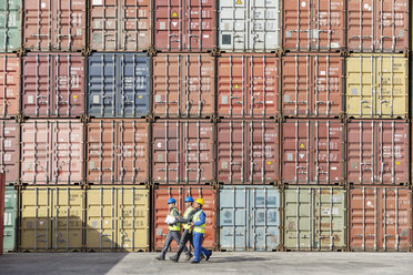 Workers walking together near stack of cargo containers - CAIF15085