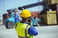 Worker using walkie-talkie near cargo containers - CAIF15088