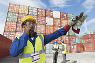 Worker using walkie-talkie near cargo containers - CAIF15103