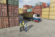 Businessmen and worker talking near cargo containers - CAIF15112