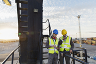 Workers using walkie-talkie on cargo crane - CAIF15115