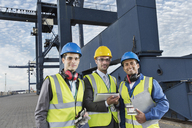 Workers and businessman smiling near cargo crane - CAIF15121