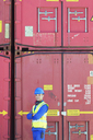 Worker smiling near cargo containers - CAIF15127