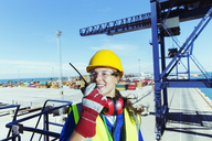 Worker using walkie-talkie on cargo crane at waterfront - CAIF15136