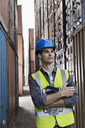 Worker standing between cargo containers - CAIF15139