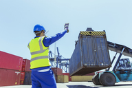 Worker directing crane carrying cargo container - CAIF15148