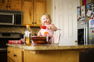 Girl eating chocolate while sitting on kitchen island - CAVF06068