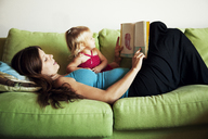 Woman reading picture book for daughter while lying on sofa at home - CAVF06089